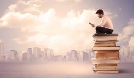 Uomo d'affari con il computer portatile che si siede sui libri Immagini Stock