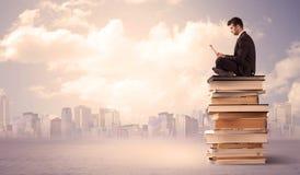 Uomo d'affari con il computer portatile che si siede sui libri Fotografia Stock