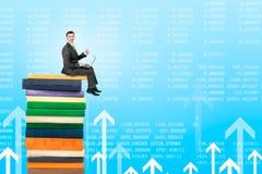 Uomo d'affari con il computer portatile che si siede sul mucchio dei libri Fotografia Stock Libera da Diritti