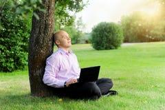 Uomo d'affari con il computer portatile che si siede vicino ad un albero Immagini Stock Libere da Diritti