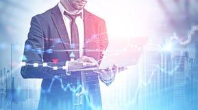 Uomo d'affari con il computer portatile in città, diagrammi immagine stock