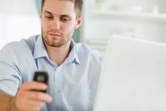Uomo d'affari con il computer portatile ed il telefono mobile Immagini Stock
