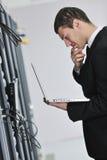 Uomo d'affari con il computer portatile nella stanza del servizio rete Fotografia Stock Libera da Diritti