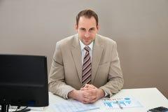 Uomo d'affari con il diagramma di Gantt che si siede allo scrittorio Fotografie Stock Libere da Diritti