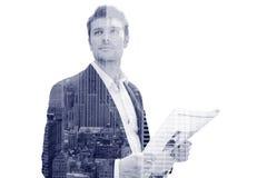 Uomo d'affari con il giornale che sta sulla via fotografia stock