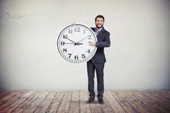 Uomo d'affari con il grande orologio rotondo in sue mani Fotografie Stock