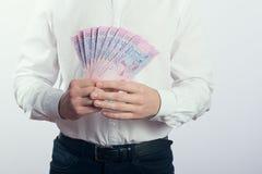 Uomo d'affari con il hryvnia in sue mani Fotografia Stock Libera da Diritti