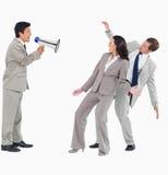 Uomo d'affari con il megafono che grida ai colleghi Immagini Stock