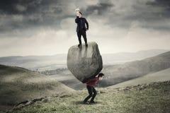 Uomo d'affari con il megafono sopra una pietra e un partner Fotografie Stock Libere da Diritti