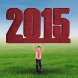 Uomo d'affari con il numero 2015 sul prato Immagini Stock Libere da Diritti