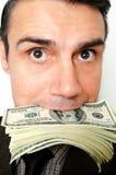 Uomo d'affari con il pacchetto dei dollari in una bocca Immagini Stock