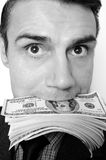Uomo d'affari con il pacchetto dei dollari in una bocca Immagini Stock Libere da Diritti