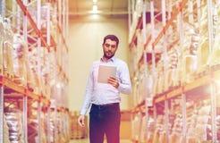 Uomo d'affari con il pc della compressa al magazzino Fotografia Stock Libera da Diritti