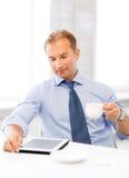 Uomo d'affari con il pc ed il caffè della compressa in ufficio fotografie stock libere da diritti