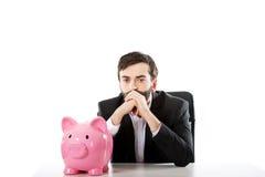 Uomo d'affari con il porcellino salvadanaio da uno scrittorio Immagine Stock Libera da Diritti