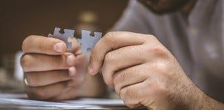 Uomo d'affari con il puzzle a disposizione Fuoco a disposizione Concetto fotografia stock