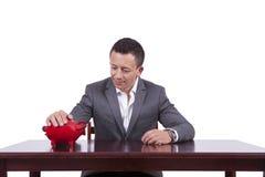 Uomo d'affari con il suo porcellino salvadanaio sul lavoro Immagini Stock Libere da Diritti