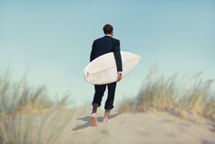 Uomo d'affari con il surf che va alla spiaggia Fotografia Stock