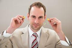 Uomo d'affari con il tappo per le orecchie fotografia stock libera da diritti