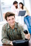 Uomo d'affari con il telefono all'ufficio Immagine Stock