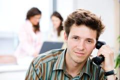 Uomo d'affari con il telefono all'ufficio Immagini Stock Libere da Diritti