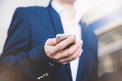 Uomo d'affari con il telefono a disposizione Immagine Stock