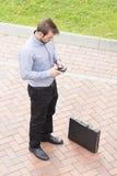 Uomo d'affari con il telefono e la cartella nella via. Fotografia Stock