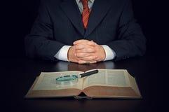 Uomo d'affari con il vecchio libro e la lente d'ingrandimento Immagini Stock