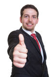 Uomo d'affari con il vestito nero che mostra pollice Fotografie Stock