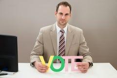 Uomo d'affari con il voto multicolore di parola Fotografie Stock Libere da Diritti