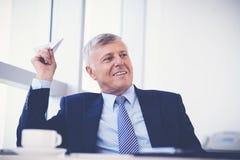 Uomo d'affari con l'aereo di carta Immagini Stock
