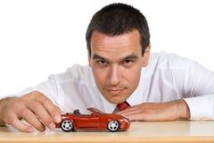 Uomo d'affari con l'automobile del giocattolo - isolata Fotografia Stock