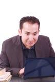 Uomo d'affari con l'espressione stupita per mezzo di un computer portatile immagine stock