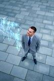Uomo d'affari con l'ologramma della mappa di mondo all'aperto Immagini Stock