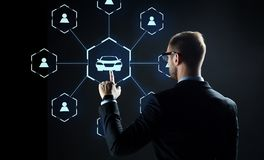 Uomo d'affari con l'ologramma virtuale del car sharing immagine stock