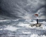 Uomo d'affari con l'ombrello durante la tempesta nel mare Concetto di protezione di assicurazione immagine stock