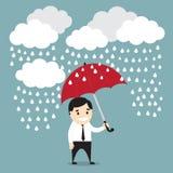 Uomo d'affari con l'ombrello rosso nella pioggia con le nuvole Sicurezza co Fotografia Stock