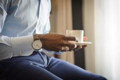 Uomo d'affari con l'orologio sul suo caffè bevente di mattina del polso fotografia stock