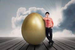 Uomo d'affari con l'uovo dorato all'aperto Immagini Stock