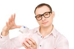 Uomo d'affari con la banca piggy ed i soldi Fotografia Stock Libera da Diritti