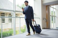 Uomo d'affari con la borsa del carrello facendo uso del telefono cellulare Fotografia Stock Libera da Diritti