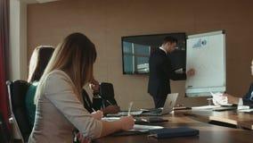 Uomo d'affari con la compressa alla riunione video d archivio