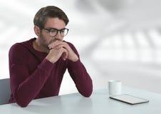 Uomo d'affari con la compressa allo scrittorio con fondo luminoso Fotografia Stock