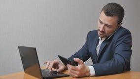 Uomo d'affari con la compressa ed il computer portatile del telefono Immagini Stock