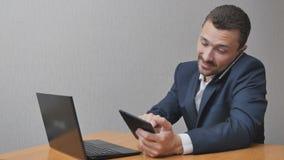 Uomo d'affari con la compressa ed il computer portatile del telefono video d archivio