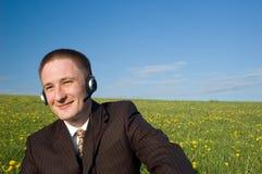 Uomo d'affari con la cuffia avricolare ed il computer portatile esterni Fotografia Stock Libera da Diritti