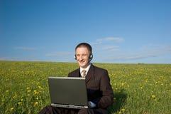 Uomo d'affari con la cuffia avricolare ed il computer portatile esterni Fotografie Stock Libere da Diritti