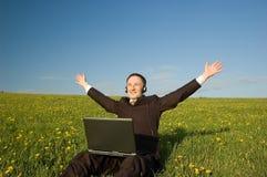 Uomo d'affari con la cuffia avricolare ed il computer portatile esterni Fotografie Stock