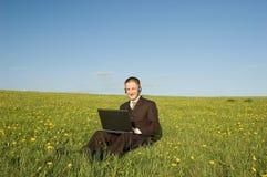 Uomo d'affari con la cuffia avricolare ed il computer portatile esterni Immagini Stock
