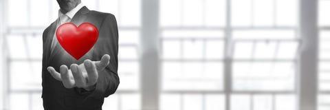 Uomo d'affari con la mano ed il cuore aperti davanti alla finestra Fotografia Stock